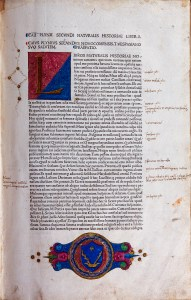 A page of Latin text with an illuminated intial letter L and a coat of arms.