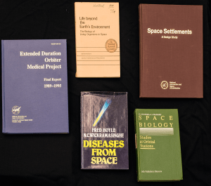 A group of five books related to medicine and spaceflight.