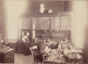 Black and white historical photograph of men in suits and aprons at work in a laboratory.