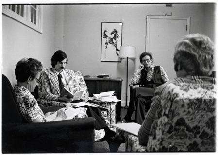 Men and women sit in armchairs reviewing books and papers.