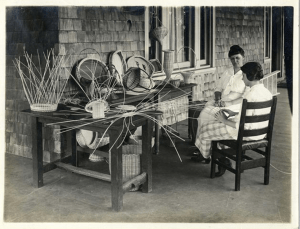Two women sit outside on a porch, one is weaving a basket, partially finished baskets sit on a table.