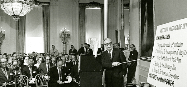 A man at a podium points to a poster in front of an audience of about 50.