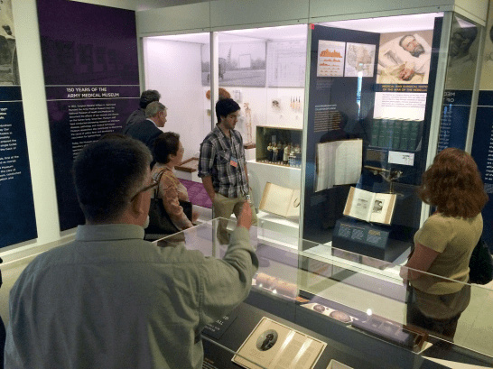 A group of people peruse a musem gallery, one case holds a multiple volumes of thick books.