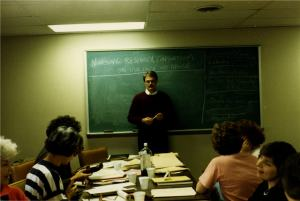 A candid photo of Dan Shridan in front of a chalkboard facing a group of women around a table piled with papers.