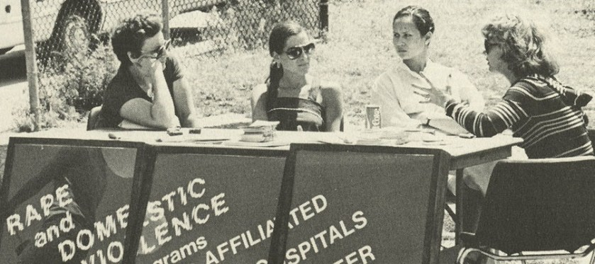 "Four women sitting at a table with identifying sign that reads ""Rape and Domestic Violence Programs at the Affiliated Hospitals Center""."