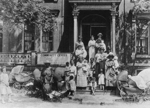 Women with children and baby carriages stand outside a building.
