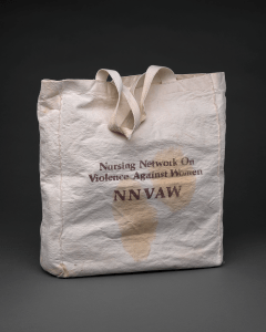 A cloth totebag with the text Nursing Network on Violence Against Women NNVAW printed on it.