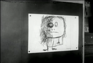 A rough sketch of a person with one dark eye and scribbles over part of the face pinned to a blackboard.