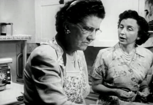 A younger woman speaks to a frownging older woman as they work in a kitchen.