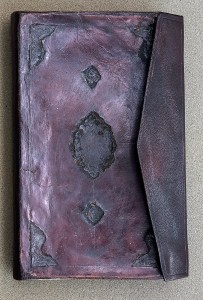 A book with a tooled leather cover and a flap that wraps around for closure.