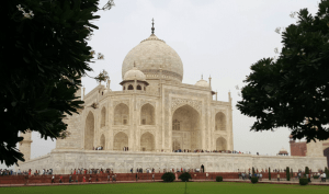 A snapshot of the Taj Mahal at an angle on a cloudy day with trees in the foreground.