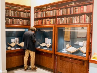 A man looks into a display case in a room lined with bookshelves.