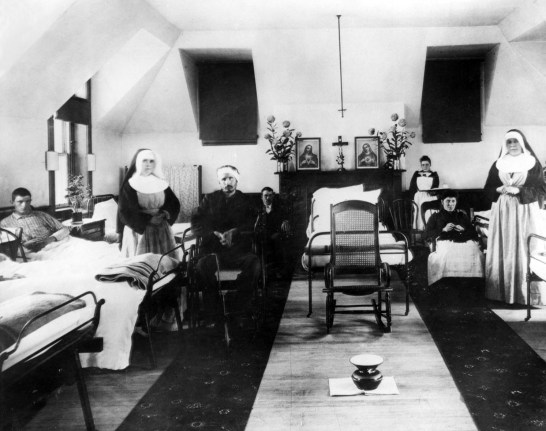 Nurses and patients in an upper story room with rows of beds.