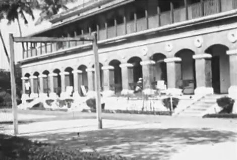 A large building with a long colonnaded porch in a tropical setting.
