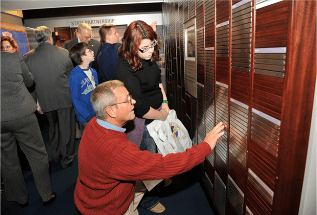 People touch and look at a wall of nameplates.
