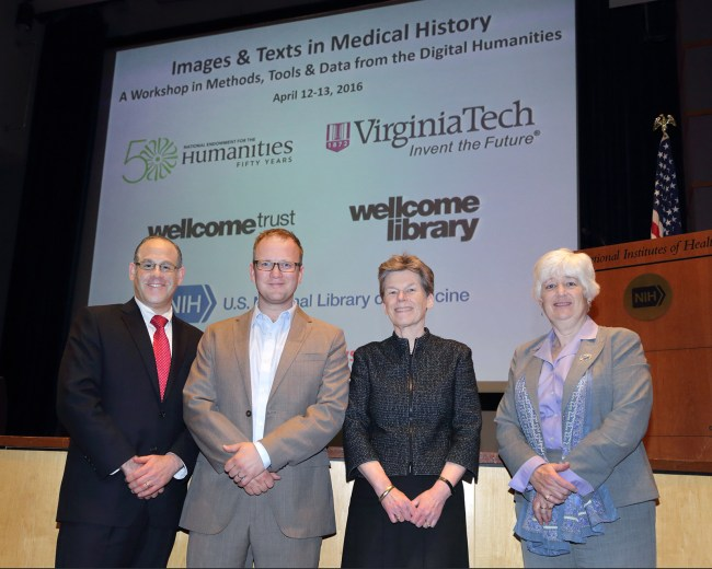 Four people stand in front of a presentation screen Reading Images & Texts in Medical History and displays the logos of involved institutions.