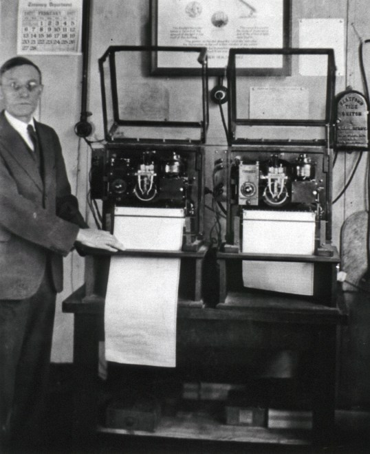 A man stands next to a recording device that measures the intensity of out-of-doors daylight in a given area