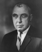 Mark Ravitch, formal head and shoulders portrait in a jacket and tie.