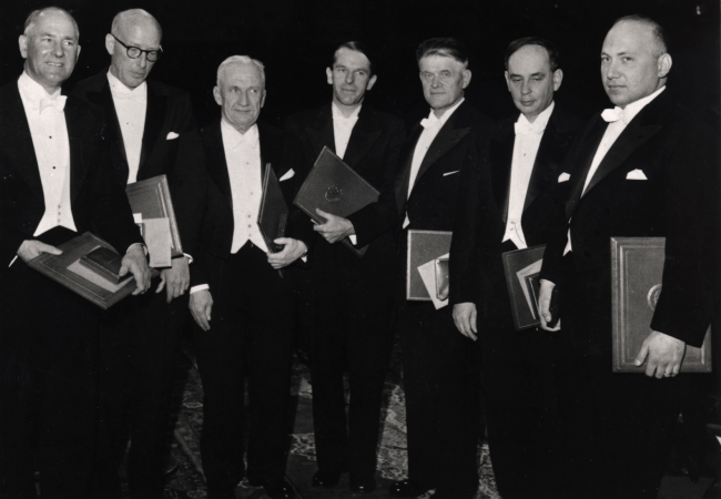 Seven men in white tie and tails stand in a group holding awards.