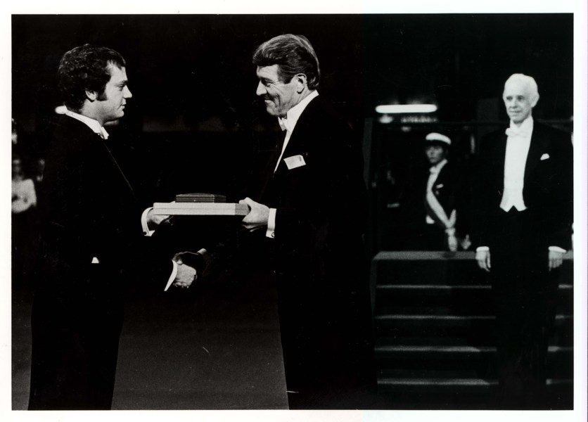 A man in evening dress recieved an award and a handshake.
