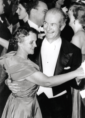 A smiling couple in evening dress dancing on a crowded floor.