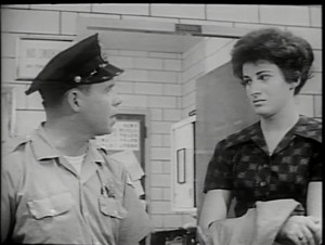 A policeman speaks with a young woman in a police station.