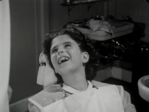 A girl in a dentist's chair, smiling.