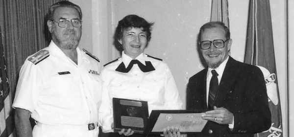 Faye Abdullah holds a plaque next to Koop, in uniform, in an office in front of flags.