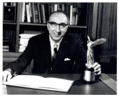 DeBakey sits at a desk smiling and holding the Laskar award, a statue of a headless woman with wings.