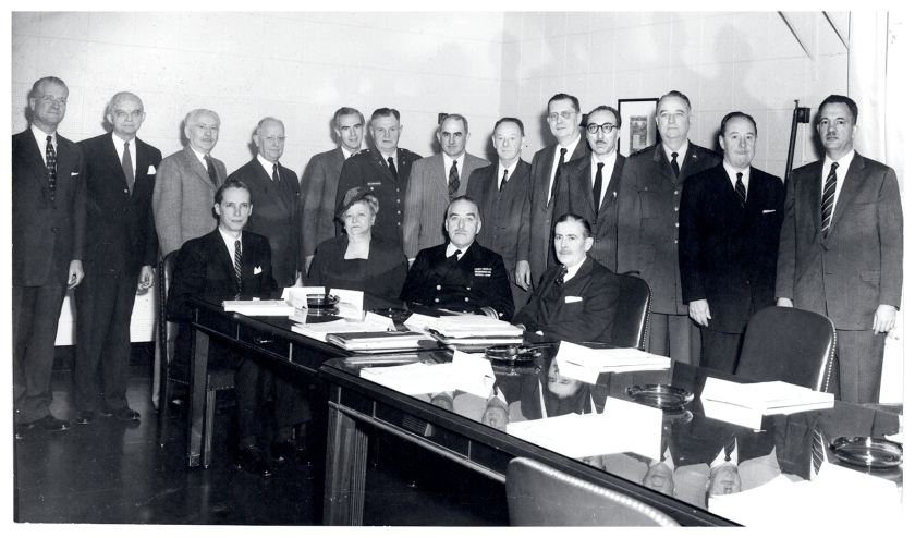 Sixteen men and a woman pose in a boardroom, DeBakey stands fourth from the right.