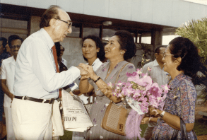 Two women greet DeBakey with handshakes and flowers.
