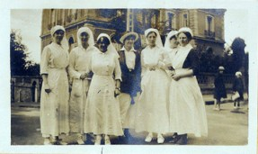 A group of nurses pose in a city.