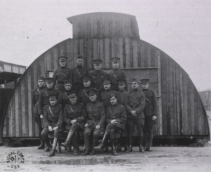 16 men in uniform pose in three rows outdoors in front of a temporary building.