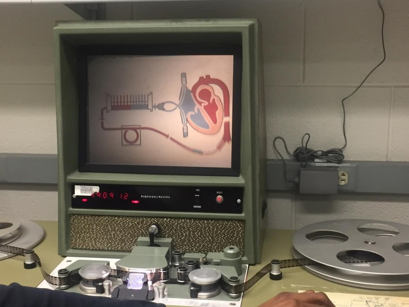 16 mm film is run from one reel to another through a machine that displays the image on a screen.