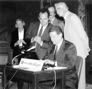 Three men and a woman watch a man using a laptop on a stage.