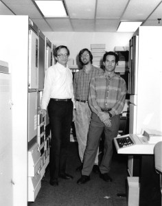 Three men stand together in a computer room.