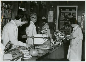 A scene resembling a small convinience store opulated with women in white medical coats.
