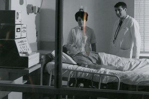 Medical personnel stand by a man laying in a hospital bed.