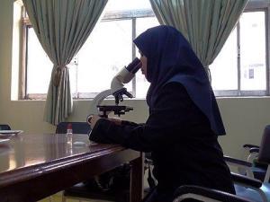 A woman looks through a microscope.