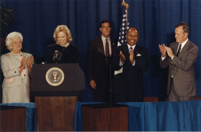 Photograph of two women on far left and three men on far right.