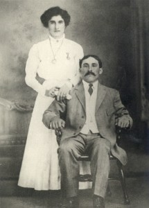 A formal portrait of a seated man and standing woman.
