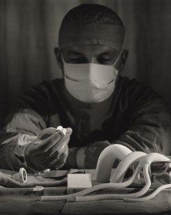 A surgeon wearing his mask sits at table, examining various artificial valves.