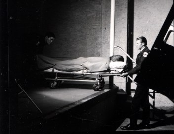 Ambulance drivers bring a patient lying on a gurney to the Emergency Room