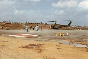 Military medical personnel hurry to a landing helecopter.