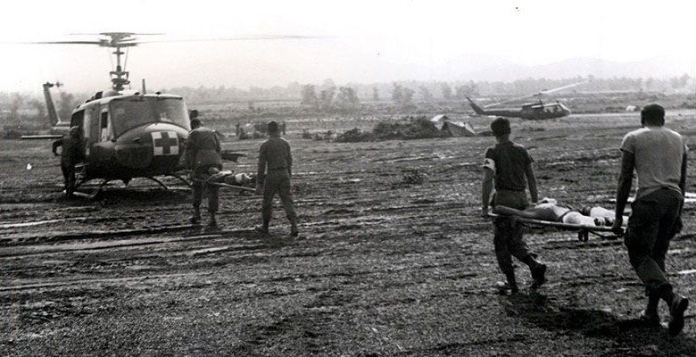 Four men cary two litters accross a muddy field to a helicopter marked with a red cross.
