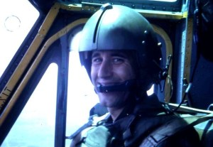 A snapshot of a young man in a flight helmet in an aircraft.