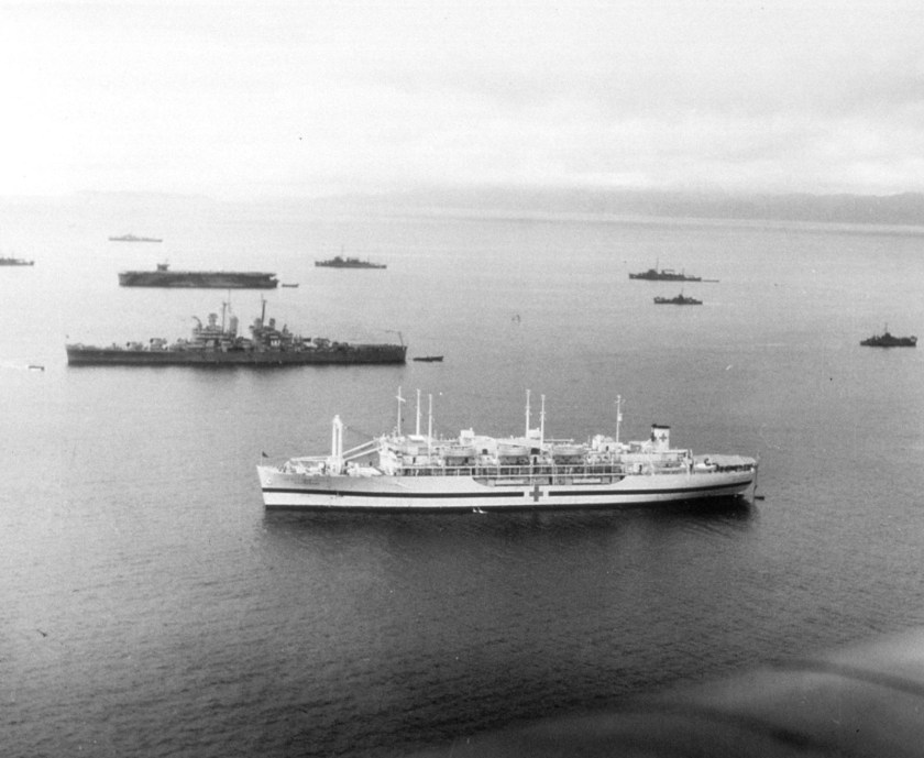 A large ship, white, marked with a red cross, surrounded by military ships.