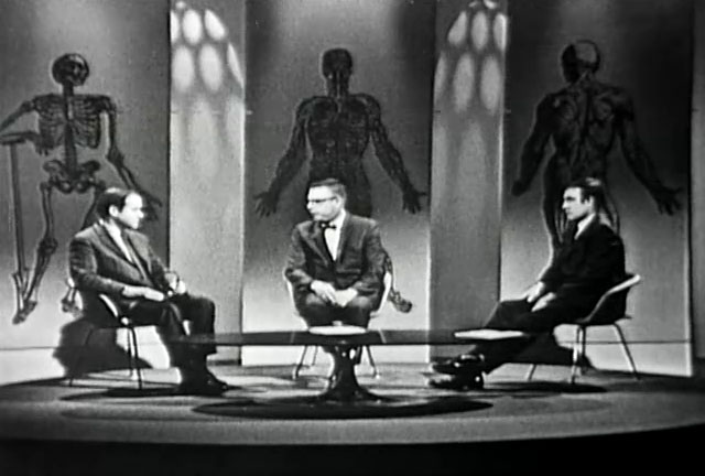 Three men in suits sit in a group around a coffee table on a TV set.