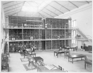 Interior view of Library Hall in the Army Medical Museum and Library, where John S. Billings is seated at a reference table and Thomas W. Wise is standing near a desk.
