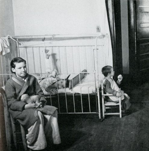 Three children patients of varying ages pass time in a room.